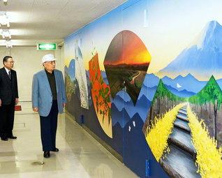 美術部の友が完成させた壁画を鑑賞する創立者・池田先生(2004年12月)。反対側の壁には、創立15周年(1986年)を記念して、当時の美術部員が制作した創大の四季を描いた壁画が