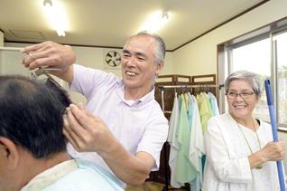 自営の理髪店で来店客の髪にはさみを入れる渡さん㊥。妻・麗子さん㊨は5年前、手術で大動脈弁狭窄症を克服し、夫の仕事を明るく支える