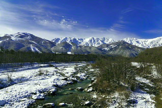 白雪に包まれた山里――奥には雪化粧した北アルプスの峰が(長野県白馬村)=長野支局