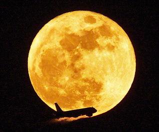 池田先生の卒寿を寿ぐように、月天子がまばゆい光を放つ。2日の満月は、月が地球に接近し、普段よりひときわ大きく見えるスーパームーン。羽田空港の上空では、鮮やかな飛行機のシルエットが浮かび上がった(本社カメラマン撮影)