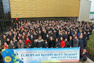 """新時代第4回「欧州広布サミット」に集った33カ国の代表・約300人。皆が「ワン・ヨーロッパ! ウィズ・センセイ!(欧州は一つ! 先生と共に!)」の合言葉を胸に刻み、そして青年の心意気で躍進することを誓い、""""青年拡大の年""""のスタートを切った(フランクフルト池田平和文化会館で)"""