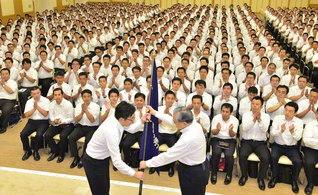 幹部会では原田会長から志賀男子部長に男子部旗が託され、場内から大拍手が。新しい「勇気」「知恵」「行動」で、創価の未来を担い立つ決意に燃えて(金舞会館で)