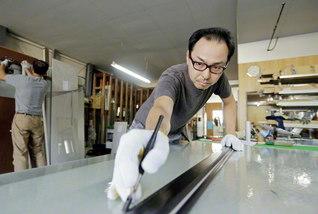 ガラス板から創作家具を作製する土山さん。どんな小さな仕事にも妥協しない、職人の意地と誇りが燃える