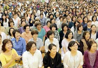 希望あふれる那覇王者県婦人部の友。寄川緑さん、安里澄子さんが、真心の語らいで信頼を広げる模様を報告(那覇西文化会館で)