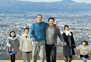 今月から壮年部として共に活動する父子。がっちり肩を組み、「これからが本門の戦いだ!」と(左から恒雄さんの長女・琴音ちゃん、母・惠美子さん、父・栄司さん、恒雄さん、妻・有里さん、次女・杏奈ちゃん)