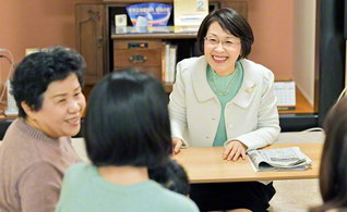 直里関西婦人部長㊨が、地域広布を支える角尾道子さん一家を激励。「母の祈りこそ、一切の悩みを乗り越える力です」と(9日、大阪市内で)