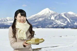 「豊かな自然に育まれた福島の米を味わってほしい!」と星野さん。後ろは雪化粧した磐梯山と猪苗代湖