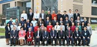 池田大作教育思想国際学術シンポジウムの参加者が記念のカメラに。後方は、シンポジウムと写真展の会場となった図書館(佛山市で)