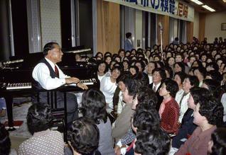 """兵庫の尼崎文化会館(現・尼崎平和会館)を訪れ、参加者に真心からの励ましを送る池田SGI会長。当時は、宗門から""""会員に指導をするな""""との卑劣な要求が出されていた。SGI会長はピアノを奏で、""""常勝の母""""たちをたたえた(1981年3月)"""