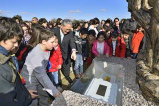 池田青年文化センターの起工式。青年部・未来部の代表が、原田会長と共に、決意文や署名等が収められたカプセルを見つめる(カニュエラスで)