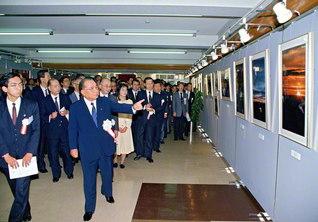 池田先生が、学生・教職員らと創立20周年記念写真展を鑑賞(1989年11月、創価大学で)。先生はこれまで写真部に対し、「心は宇宙より広い」「心 心 心 写真なり」などの揮毫(きごう)を贈ってきた