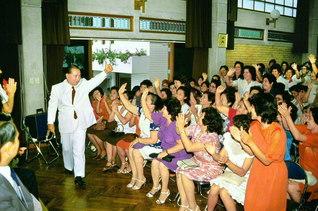 """10年ぶりにペルーを訪問した池田先生が、広布20周年記念の勤行会に出席。計2500人の参加者と3度にわたり勤行・唱題を行い、故・キシモト初代理事長の功労を称賛するとともに、""""妙法こそ幸福の原動力である""""と呼び掛けた(1984年3月4日、リマのペルー文化会館で)"""