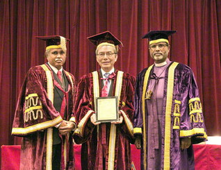 池田先生に贈られた顕彰状の授与式。バルギース学長㊧、創価大学の馬場学長、マッシ主教㊨が祝福のカメラに