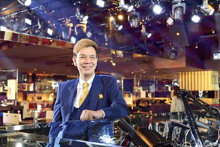 スーツを華麗にまとい、ホールに立つ熊谷さん。「皆に楽しんでもらえるよう、誠実にお客さまと接しています」と