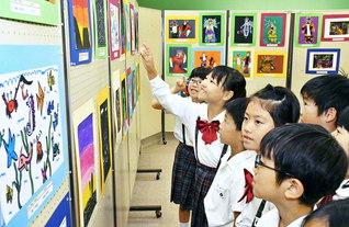 北京第一小学校の子どもたちが描いた作品を、楽しそうに見つめる関西創価小学校の児童(枚方市で)