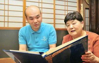 挑戦の歴史がつづられたアルバムを手に、来し方を語らう桑畑さん㊧と母・三枝子さん。思い出話に花が咲く