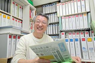 """堂々と並ぶファイルブックを背に、切り抜きを手にする山内さん。「聖教新聞を愛する""""聖教オタク""""として、まずは1000冊の切り抜きを」と、会心の笑顔で胸を張る"""