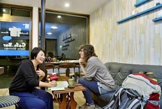 佐藤さん㊧が経営する「ゲストハウス佐藤商店」はJR豊浦駅の目の前に。外国人旅行客の憩いの場だ