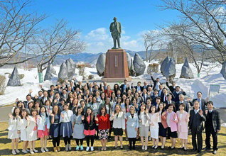 雪の戸田記念墓地公園を訪れ、世界広布の誓いを新たにした海外の同志を、戸田先生の立像が見つめる。池田先生はこれまで11度にわたって厚田を訪れ、恩師と不二の共戦譜をつづってきた。そして今、創価の師弟のバトンは世界の池田門下に受け継がれる(石狩市厚田区で)