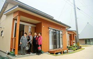 西原村の災害公営住宅で。久保田十三子さん(左端)のもとを地域の同志が訪ねる