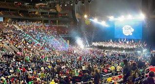 誓いと歓喜みなぎるニューヨーク会場の大会。日本など世界各国の青年部から寄せられた祝福のビデオメッセージが紹介された(ニュージャージー州ニューアークのプルデンシャルセンターで)