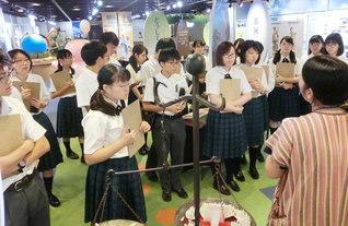 JICA地球ひろばで、ガイドの説明を受ける東京・創価高校の生徒。世界の食糧事情を学ぶ企画展示などを見学した