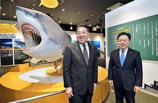 「小さなお子さまでも楽しんでいただけるよう工夫を凝らしています」と、ホホジロザメの実物大模型の前で語り合う清水社長㊧と新沼東北青年部長