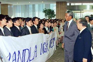 池田先生が南アフリカのネルソン・マンデラ大統領(当時はアフリカ民族会議副議長)を、青年の代表らと共に歓迎。創大パン・アフリカン友好会の友が、同国の愛唱歌「ロリシャシャ・マンデラ」を真心を込めて合唱した(1990年10月31日、東京・信濃町の聖教新聞本社で)。マンデラ大統領には95年7月、創価大学の名誉博士号が贈られている