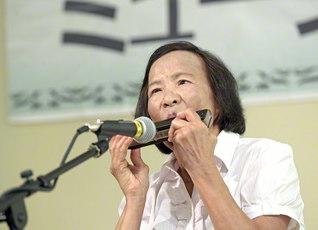 奈良県立美術館でクロマチックハーモニカを披露する田中さん。経験談を語りつつ、1時間のコンサートを