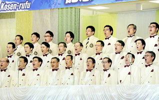 """王者のごとき威風堂々の前進を!――創価合唱団の代表、さらに音楽隊・しなの合唱団が、音楽隊・創価グロリア吹奏楽団の演奏に乗せて、「滝の詩」と""""大楠公""""を力強く歌い上げた(神奈川池田記念講堂で)"""
