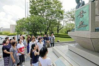 「学光の塔」を仰ぎ見る通教生。塔を飾る男女6体の像は「挑戦」「情熱」「歓喜」「英知」「行動」「青春」のテーマを表現している